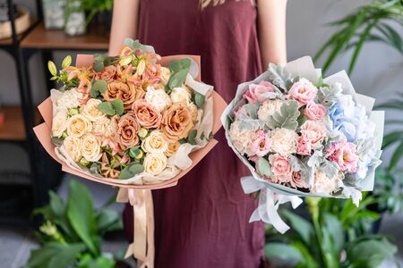 Two beautiful bouquets of mixed flowers in woman hand. Floral shop concept . Handsome fresh bouquet. Flowers delivery. Imagens