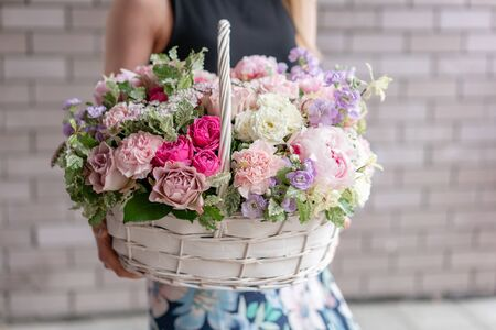 Wicker basket. Beautiful bouquet of mixed flowers in woman hand. Floral shop concept . Handsome fresh bouquet. Flowers delivery