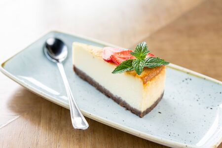 Piece of delicious cheesecake with strawberry and mint leaves on white plate 写真素材
