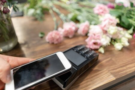 Concept contactless payment. Making payment with smartphone and pos terminal, printed check. Floral shop concept . Flowers delivery Stockfoto
