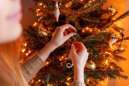 Happy young woman decorating christmas tree at home. Winter holidays in a house interior. Golden and white Christmas toys, lights garlands. Natural Danish spruce 版權商用圖片