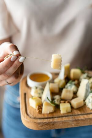 Girl holding piece of parmesan cheese on a skewer and wooden plate with cheese. Delicious cheese mix with walnuts, honey. Food for wine.