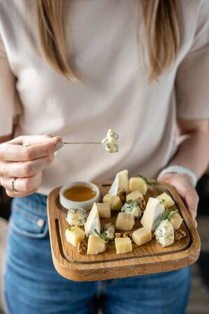 Girl holding piece of Gorgonzola cheese on a skewer and wooden plate with cheese. Delicious cheese mix with walnuts, honey. Food for wine.