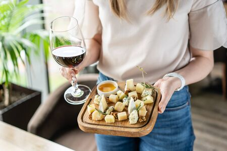Girl holding glass red wine and wooden plate with cheese. Delicious cheese mix with walnuts, honey. Tasting dish on a wooden plate. Food for wine. Stok Fotoğraf