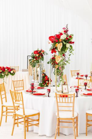 Beautiful banquet hall under a tent for a wedding reception. Interior of a wedding tent decoration ready for guests. Decor flowers. Red theme