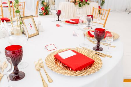 Table setting red napkins and glasses, gold plates. Interior of a wedding tent decoration ready for guests. Decor flowers. Red theme Archivio Fotografico