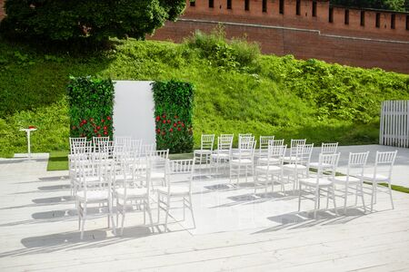 Rows of empty white chairs sitting on a wooden floor. Wedding chairs with flowers at ceremony outdoors