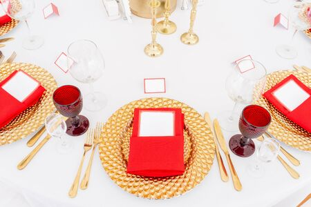 Table setting red napkins and glasses, gold plates. Interior of a wedding tent decoration ready for guests. Decor flowers. Red theme