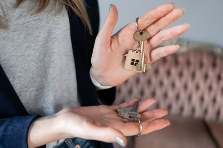 Mortgage. The concept of choice. Keys to two apartments. Young pretty woman. two house keys in womans hands. . Modern light lobby interior. Real estate, hypothec, moving home or renting property.