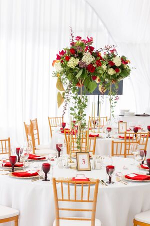 Red decor theme. Beautiful banquet a wedding reception. Interior of a wedding tent decoration ready for guests. Decor flowers. Archivio Fotografico