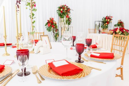 Table setting red napkins and glasses, gold plates. Interior of a wedding tent decoration ready for guests. Decor flowers. Red theme Stock fotó
