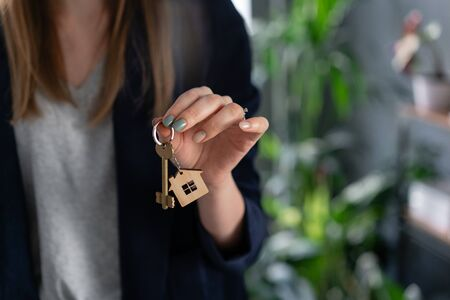 Mortgage concept. Young pretty woman. two house keys in womans hands. . Modern light lobby interior. Real estate, hypothec, moving home or renting property. Stock Photo