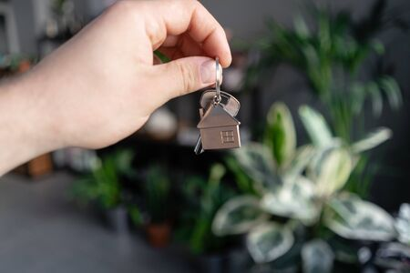 Concept of renting an apartment. House key in man hands. Young woman. Modern light lobby interior. Real estate, hypothec, moving home or renting property.