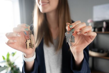 Young pretty woman smiles. House key in womans hands. . Modern light lobby interior. Real estate, hypothec, moving home or renting property.