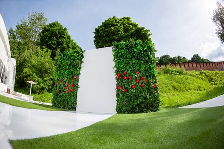 Beautiful setting for outdoors wedding ceremony waiting for bride and groom and guests. Wooden chairs decorated with flowers, are in the zone of the wedding ceremony in a park