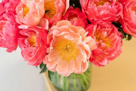Peonías de coral en un jarrón de cristal sobre mesa de madera .. Hermosa flor de peonía para catálogo o tienda online. Concepto de tienda floral. Hermoso ramo recién cortado. Entrega de flores. Copia espacio