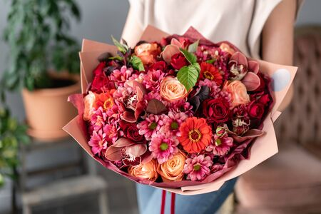 Wine color. Beautiful bouquet of mixed flowers in womans hands. the work of the florist at a flower shop. Fresh cut flower.
