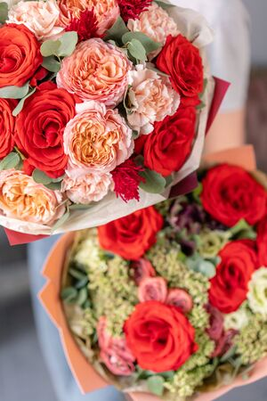 Two Beautiful bouquets of mixed flowers in womans hands. the work of the florist at a flower shop. Fresh cut flower. Red and pink color Imagens