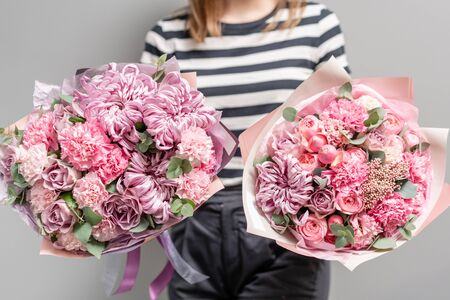 Two Beautiful bouquets of mixed flowers in womans hands. the work of the florist at a flower shop. Delicate Pastel color. Fresh cut flower. Pink color