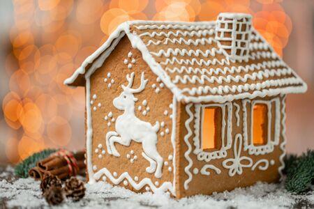Lebkuchenhaus auf dem Tisch. Defokussierte Lichter der Weihnachtsgirlande. Morgen im hellen Wohnzimmer. Urlaubsstimmung. Figur Hirsch