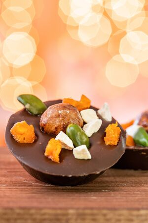 Christmas theme. Handmade chocolates candy. Mini chocolate dessert covered with nuts and dried fruits. Garland lamps bokeh on background. Copy space Stok Fotoğraf