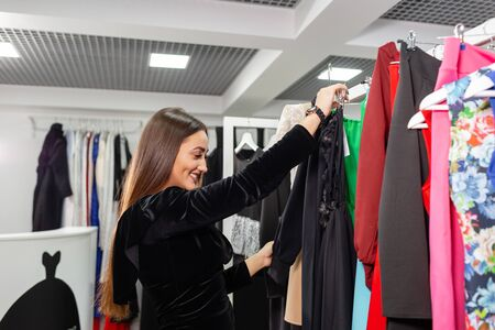 Happy young woman choosing clothes in mall or clothing store. Sale, fashion, consumerism concept Stockfoto