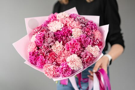 Mono bouquet. Bunch of carnation flowers rich pink color. Spring bunch in woman hand. Present for Mothers Day.