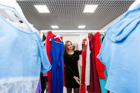 Happy young woman choosing clothes in mall or clothing store. Sale, fashion, consumerism concept Stockfoto - 130737222