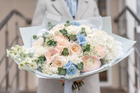 Nice bouquet of mixed flowers in woman hand. Pink and white color. the work of the florist at a flower shop. Delicate Pastel color. Fresh cut flower.