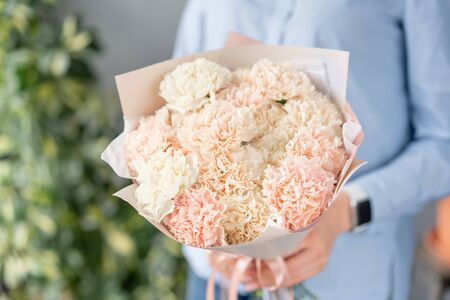 Mono bouquet. Bunch of carnation flowers pastel color. Spring bunch in woman hand. Present for Mothers Day.