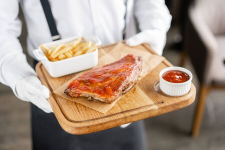 The waiter is holding a wooden plate Delicious Pork ribs. Full rack of ribs BBQ on wooden plate with french fries and salad