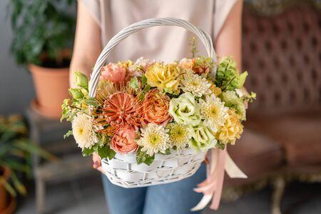 Bloemstuk in rieten mand. Mooi boeket van gemengde bloemen in de hand van de vrouw. Bloemen winkelconcept. Knap fris boeket. Bloemen bezorgen