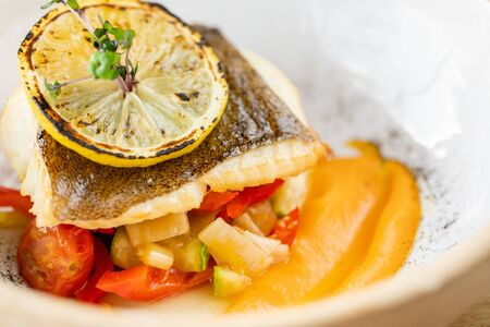 Roasted pike perch or cod fish with baked vegetables. Dish decorated with a slice of lemon. Restaurant menu