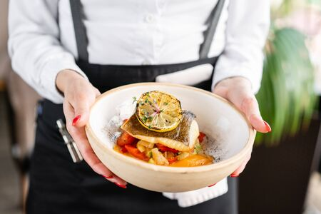 The waiter is holding a plate Roasted pike perch or cod fish with baked vegetables. Dish decorated with a slice of lemon. Restaurant menu