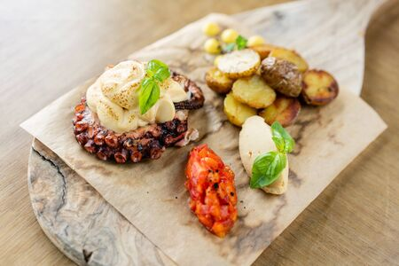 Roasted octopus BBQ with Baked potato. Wooden plate. Restaurant menu
