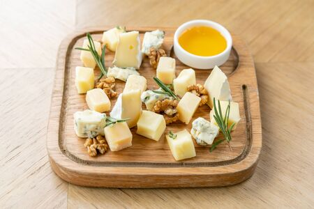Cheese plate. Delicious cheese mix with walnuts, honey on wooden table. Tasting dish on a wooden plate. Food for wine. 版權商用圖片 - 130953689