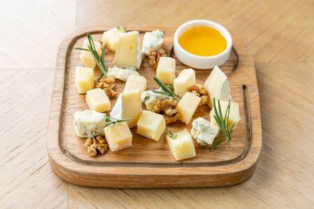 Plato de queso. Deliciosa mezcla de queso con nueces, miel de mesa de madera. Plato de degustación en un plato de madera. Comida por vino.