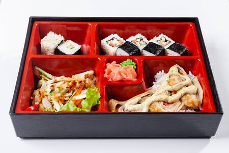 Fresh food portion in japanese bento box with salad, main course. Sushi roll with vegetables. Vegetarian dish. Stock Photo