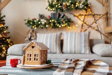 La mattina di Natale nel luminoso soggiorno. Casa di pan di zenzero fatta in casa sulla stanza di sfondo decorata per il Natale.