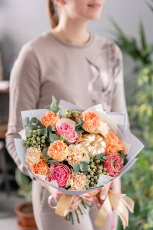 Beautiful bouquet of mixed flowers in womans hands. the work of the florist at a flower shop. Fresh cut flower.
