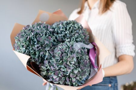 Bouquet of purple and green flower. Beautiful hydrangea flowers in womans hands. the work of the florist at a flower shop. Fresh cut flower.