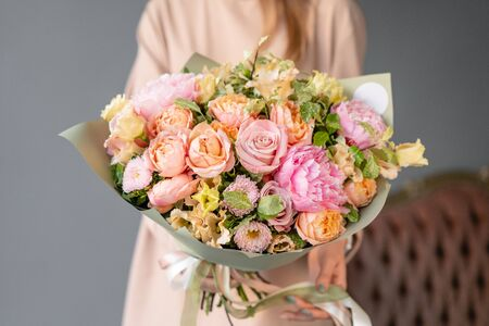 Small Beautiful bouquet of mixed flowers in woman hand. Floral shop concept. Flowers delivery. Pink peonies