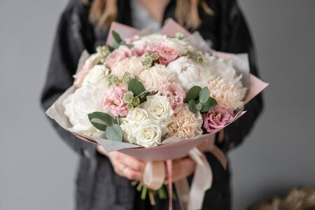 Small Beautiful bouquet of mixed flowers in woman hand. Floral shop concept. Flowers delivery. White peonies