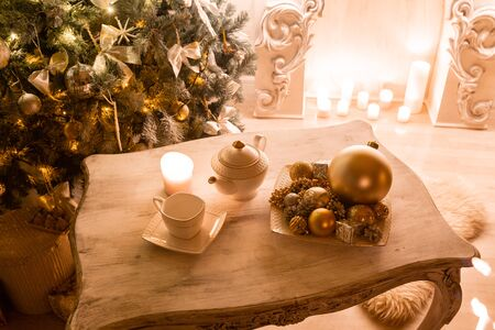 Tea time, white teapot and cups on the table. Decorated Christmas tree. Classic apartments with a white fireplace.
