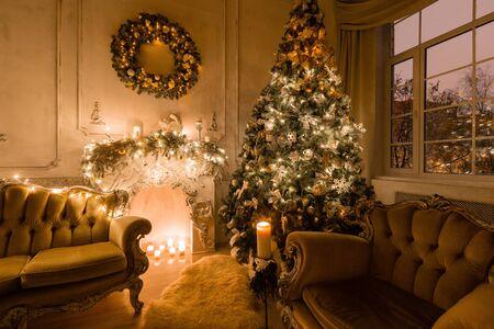 Serata di Natale a lume di candela. appartamenti classici con camino bianco, albero decorato, divano, ampie finestre e lampadario.