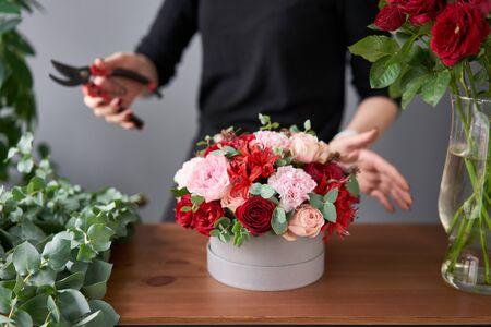 Florist woman creates flower arrangement in a round box. Beautiful bouquet of mixed flowers. Floral shop concept . Handsome fresh bunch. Stock fotó