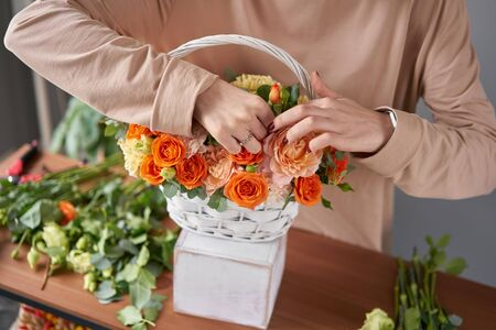 Florist woman creates flower arrangement in a wicker basket. Beautiful bouquet of mixed flowers. Floral shop concept . Handsome fresh bouquet. Stock fotó