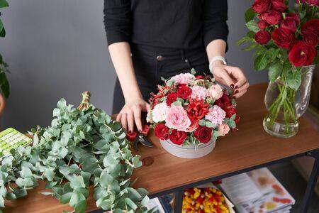Florist woman creates flower arrangement in a round box. Beautiful bouquet of mixed flowers. Floral shop concept . Handsome fresh bunch. Фото со стока