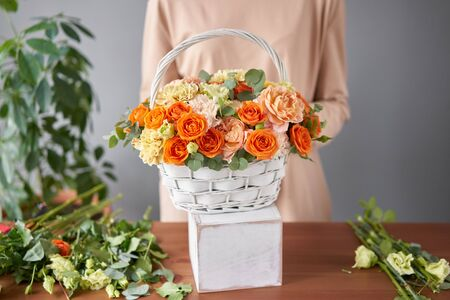 Florist woman creates flower arrangement in a wicker basket. Beautiful bouquet of mixed flowers. Floral shop concept . Handsome fresh bouquet. Flowers delivery