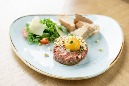 Beef tartar in the restaurant. Tasty dish on a plate. Restaurant menu.